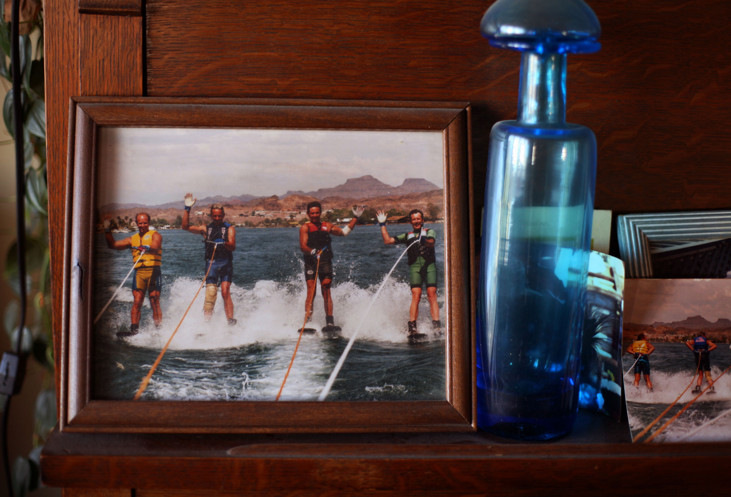 Photographs and antique bottles line the shelves inside Johnny O's home. He's second from left here in his younger days on the water, where he is the happiest.