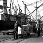 Longshoremen load cargo from a rolling pallet onto a ship anchored by the dock at the Port of Los Angeles in 1939. Courtesy: WPA collection at the Los Angeles Public Library